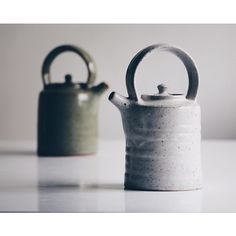 A pair of teapots, matte white and crackle green blurred behind.