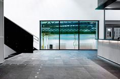 For the interiors, the practice wanted to emulate the caves and rock formations found in the Norwegian landscape. Dark stone tiles with integrated benches and seating areas are heated to emulate the stone plateaus that catch the sun on the mountainsides near lakes and natural pools. White Ceiling, White Walls, Diving Pool, Yellow Tile, Metal Facade, Nordic Lights, Clerestory Windows, Building A Pool, Ground Floor Plan