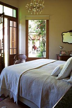 Dormitorio romántico con vista a una galería, gran araña colgante y textiles nobles en una casa reciclada del Bajo San Isidro.