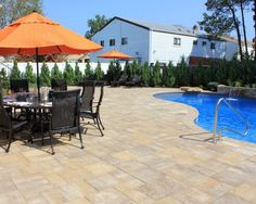 This beautiful Long Island backyard was created by Green Island Design using products by Cambridge Pavingstones with Armortec: Pavingstones: The Sherwood Collection, Ledgestone in Sahara Chestnut Lite.