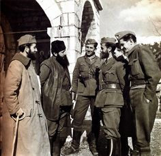 Greek Resistance, Notorious communist guerrilla leader Aris (with black cap) converses with his fighters somewhere in the mountains of central Greece. Next to him, the man with the cane is his brother. Guerrilla, Armed Forces, World War Ii, Troops, Ww2, The Man, Greece, Military, History
