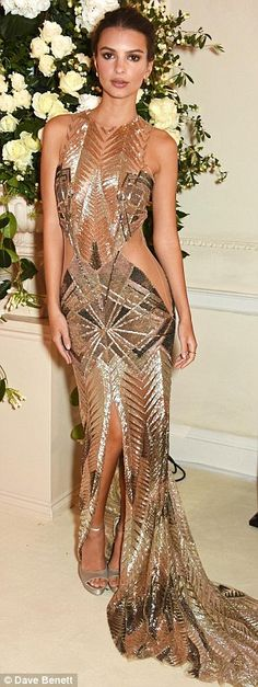 Golden girl: The We Are Your Friends actress wasn't shy flaunting her toned body in the intricate dress that boasted a saucy front slit - which paraded her slender pins as her glamorous train gathered in front of her