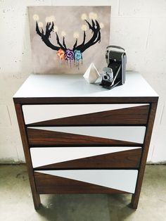 """""""Nimbus"""" chest of drawers. A gorgeous chic take on this vintage chest of drawers. Bare bones before, now refinished in a modern geometric design with kona stain by Rustoleum, and paints in white satin and silver streak semi-gloss."""
