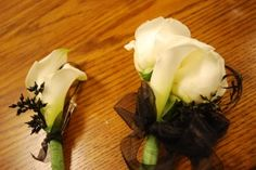 groom's boutonniere of two mini callas with sprayed black greens.  Mother of the groom corsage of roses and mini callas.