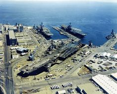 An aerial view of Hunters Point Naval Shipyard, San Francisco, California (USA), with three docked aircraft carriers on 25 August 1971; USS Ranger (CVA-61) (in dry dock), USS Coral Sea (CVA-43), and the USS Hancock (CVA-19