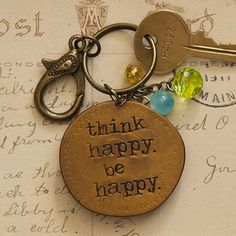 """Think Happy Junk Market Token Keychain - Junk Market Token copper keychain with """"think happy be happy"""" engraved. Pink, blue, and orange charms attached."""