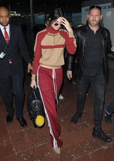 Kendall Jenner in a sporty red-and-tan Chloé tracksuit at Charles de Gaulle airport in Paris.