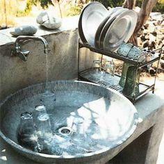 Gros plan sur l'évier de la cuisine extérieure est en fait une bassine en tôle galvanisée et assiettes en alu typique de l'artisanat grec.
