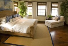 Natural wood panel hard flooring here sets off the wicker bed frame and off-white lounge chair and bedding.