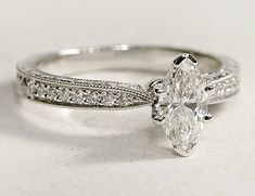 Engraved micropave diamond engagement ring set with a marquise cut diamond.