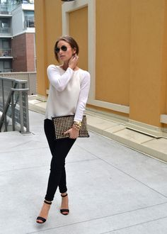 White sweater, black pants, and a great clutch. Via Chloe Rose Boutique