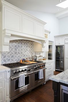 Geometric gray and white tile provide a modern backsplash above the professional grade stove in this bright, white kitchen. White counters and cabinets keep the space feeling fresh while a built-in stainless steel wine cooler is perfect for entertaining.