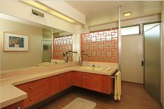 Sleek mid-century modern bathroom. Love the long counter top and the geometric orange space divider.