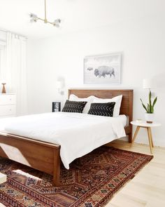 master bedroom refresh. Modern boho bedroom with wood bed and earthy antique rug.