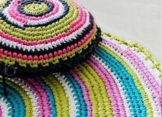 Pirteän värisistä puuvillatrikoista virkattu matto ja tyyny tuovat kotiin leikkimielisen kepeää ilmettä.
