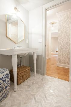 Beautiful powder room features a gold hexagon mirror illuminated by a glass and brass cone sconce, Schoolhouse Electric Princeton Sophomore Sconce, over a Parisian pedestal sink atop a marble herringbone tiled floor.
