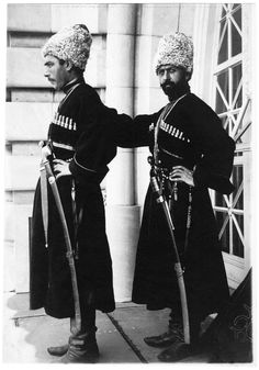 Imperial Russian Army - Cossacks each wearing 1910 model Papakha hat with wool top. Distinctive Cossack Short Sword Kindjal Daggers and Caucasian/Circassian Shashqua (sabers) are displayed.  Both are wearing the classic, long cherkesska coats. WW1 circa 1917.