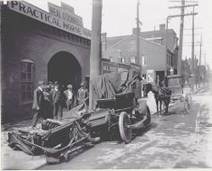 Scene: Wrecked car parked outside of Neal O'Donnell's Practical Horse Shoeing shop, St. Louis, 1908. Get a horse!