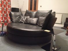 Fabulous leather 2 person large swivel snuggler chair/sofa.  Perfect for this music room.