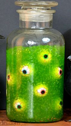 DIY Slimy Eye of Newt Jar ~ easy and fun Halloween party decor... made with small tapioca pearls, food coloring (electric green), glow sticks and eyeball super balls