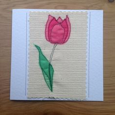 These simple but delicate tulip flowers were made by sewing organza onto a canvas background. The finished result is similar to that of a painted picture but far more special and unique. The needle was my pen and the fabric was my paint. This card would shine out from any others in a line up. It would be perfect for framing as a special memento to keep long after the event. Each card is individually handmade by me in my studio so small variations from the one in the photo make it uniquely…