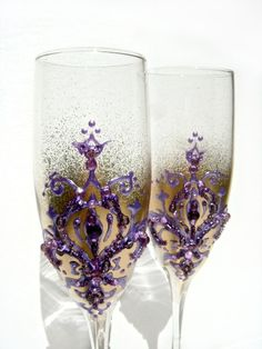 Wedding champagne glasses with a fleur-de-lis decoration in gold and lavender/purple on Etsy, $52.00