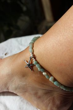 Beautiful Aquamarine and Sterling Silver Anklet.  In this Beach and Summer Anklet I have used Aquamarine Small Nuggets and Sterling Silver Stardust Beads and a Sterling Silver Starfish Charm. Clasp is a small lobster clasp.  Anklet is 10 inches.  For more Anklet Designs and other jewelry creations please visit my shop:   https://www.etsy.com/shop/EarthSeaSkyJewelry?ref=hdr_shop_menu   Member of HandMade in USA team of over 400 Artists & Designers, over 4000 items...