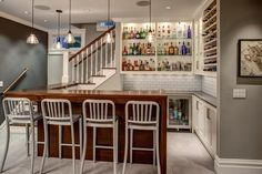 The basement bar uses space that would otherwise be empty square footage. A custom bar aligns with the stair treads and is the same wood and finish as the steps. A dark charcoal wall is a complementary accent to the light gray paint. Glass subway tile adds a simple pattern to the space and open shelving keeps bottles organized and accessible.