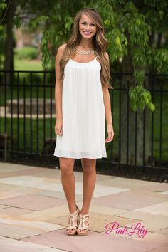 This classic little white dress will have you feeling like a goddess! It features pleats on the front and back, soft and airy material, adjustable spaghetti straps, and a plain cream band at the top of the bust.