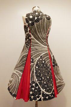 Das Reißverschlußkleid in dynamischem schwarz weiss Muster kombiniert mit knalligen rot Falten. (Ansicht von hinten, mit geöffneten Falten)