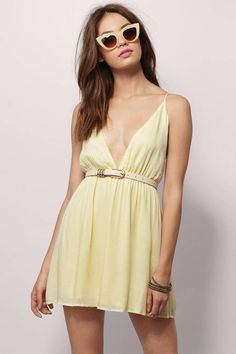 Strappy sleeveless skater dress with A line silhouette, deep plunge neckline, and caged tie back. Wear with ankle strap sandal heels for a beach day.