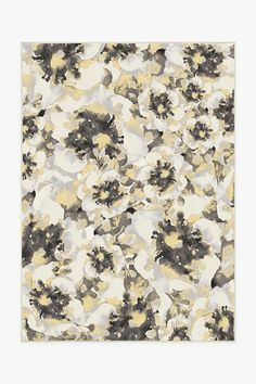 This Buttercup Yellow rug features a watercolor floral motif of overlapping blooms in white and soft yellow with accents of grey.