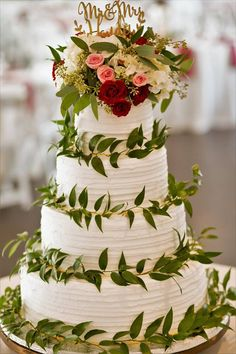A stunning wedding cake accented with a floral topper and Italian ruscus accents on each layer by Stems Florist - St.Louis, MO ... a reception centerpiece for any wedding!