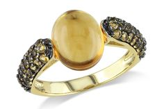 This charming ring features an oval-cut citrine center stone and round-cut citrine side stones set in yellow and black rhodium plated sterling silver. The ring is adorned by a highly polish finished.