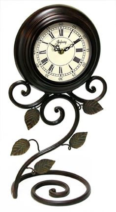 The Iron Perennial by Infinity Instruments. Metal table clock with Roman hourly numerals and Arabic minutes. #clock #tabletop #metal #flower