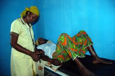 A woman receiving prenatal care including techniques of prevention against malaria.