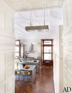 A beautiful kitchen entryway has a plasterwork ceiling and wood-paneled walls.