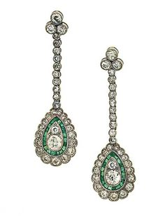A pair of diamond and emerald pendent earrings   Each old brilliant-cut diamond trefoil surmount suspending a diamond line terminating in a pear-shaped drop set with two graduated old-cut diamonds within a calibré-cut emerald and old-cut diamond surround, millegrain detail throughout, post fittings, 4.2cm long