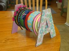 Headband holder made with oatmeal container and letters from Hobby Lobby covered in scrapbook paper and Mod Podge. Be sure to glue one letter to the lid so you can store extras inside the oatmeal tub.