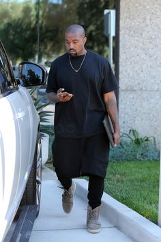 Kanye West wearing  Adidas Yeezy Boost  750, Acne Chelsea Short T-shirt, Personalized Boutique Custom Made Nori 14K Gold Raised Letter Name Bar Necklace