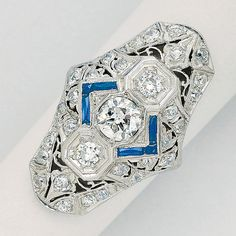 Diamond and Platinum Ring, circa 1920  Centering a round diamond weighing approximately 0.70 carat, between a pair of smaller round diamonds, amid a pierced plaque further decorated with smaller diamonds and simulated sapphire accents