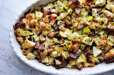 chestnut stuffing w/ leeks & apples  3 cups cubed white sandwich bread, crusts removed  4 tablespoons unsalted butter  2 cups sliced leeks {white & light green parts}  1 rib celery, chopped  1 teaspoon chopped thyme leaves  1 Granny Smith apple, peeled & diced  1/2 teaspoon kosher salt  freshly ground black pepper {to taste}  7-8 ounces bottled roasted chestnuts, coarsely chopped  1/2 cup heavy cream  1/4 cup minced fresh parsley