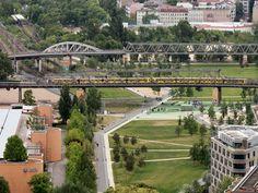 Unweit des Parkhaus Gleisdreieck passiert hier eine unbekannte U-Bahn die Brücke über den Park in dem man  entspannt flanieren kann.  Gesehen am 3. Juni 2015 vom Panoramapunkt auf dem Potsdamer Platz.