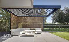 Terras met lounge en zwevende terrasoverkapping met zwarte lamellen. Mooie combinatie van houten lamellen in zijwand. Tuin en terrasidee voor zonwering en windscherm.