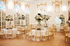 ballroom at the wimbish house in atlanta is set for the wedding reception in gold and white. lush tall arrangements on gold pedestals of all white flowers and lush greenery are a grand statement.