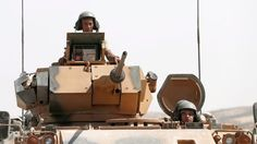 Turkish soldiers with tanks return from Syria to Turkey after a military operation at the Syrian border as part of their offensive against the Islamic State (IS) militant group