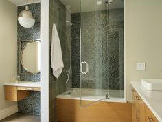 A kid-friendly bathtub is easy to step into and has an easy to open and close glass door. A low vanity and child-level mirror hangs in different part of bathroom, which is separated from shower by a tile wall.
