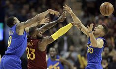 Cleveland Cavaliers' LeBron James (23) passes over Golden State Warriors' Stephen Curry (30) as Andre Iguodala (9) defends in the second half of an NBA basketball game, Sunday, Dec. 25, 2016, in Cleveland. The Cavaliers won 109-108. (AP Photo/Tony Dejak)