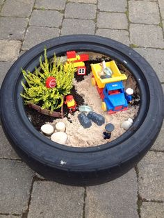 Construction small world in a tyre. Outdoor learning spaces, Outdoor play areas, Outdoor play I would love to have a large tray of grass a. Eyfs Outdoor Area, Outdoor Play Areas, Kids Garden Toys, Preschool Garden, Dinosaur Garden, Outdoor Learning Spaces, Lunch Boxe, Sensory Garden, Small World Play
