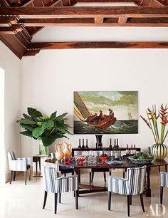 In the dining area of his Cartagena, Colombia, home, Richard Mishaan paired a majestic antique table with armchairs of his own design, clad in a Lee Jofa stripe. | archdigest.com